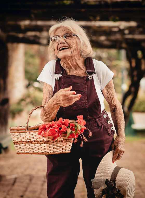 woman wearing brown dungaree pants holding sunhat and picnic basket